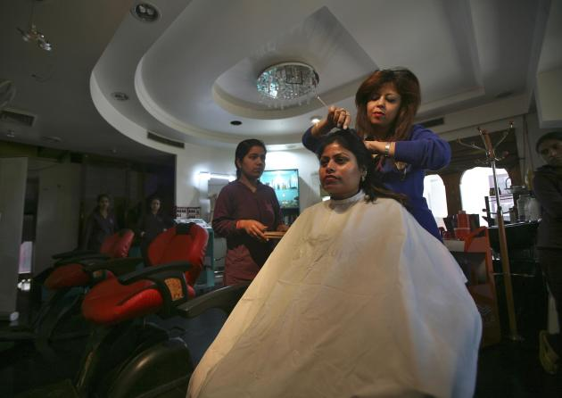 Shivani Gupta, a beautician, styles the hair of her customer inside her beauty parlour in Jammu