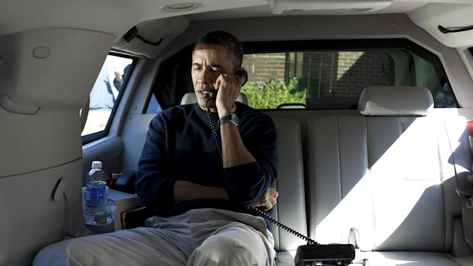 President Barack Obama talks on the phone with Afghanistan President Hamid Karzai from his vehicle outside the Jane E. Lawton Community Center in Chevy Chase, Md., Sunday, March 11, 2012. Defense Secretary Leon Panetta also called Karzai to express their condolences and vowed to hold those responsible accountable after an American soldier in Afghanistan wandered off base and allegedly gunned down more than a dozen villagers in Afghanistan.  (AP Photo/The White House, Pete Souza)