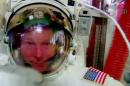 FILE - In this file image made from video provided by NASA, astronaut Terry Virts points to his helmet as he sits inside the International Space Station on Wednesday, Feb. 25, 2015, during an inspection for water in his suit. Virts reported the water while he waited in the air lock for Wednesday's spacewalk to formally conclude. On Friday, Feb. 27, 2015, NASA cleared Virts' spacesuit for the last of three spacewalks, set for Sunday. Mission managers believe they understand the quirks with this suit, and insist it is safe to use. (AP Photo/NASA, File)