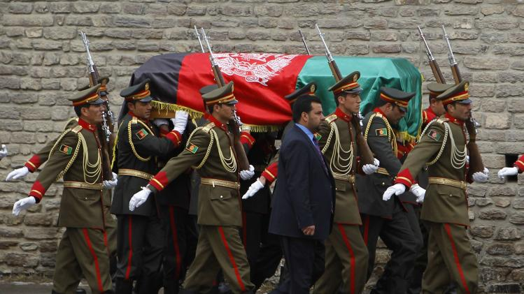 Members of the honor guard carry the flag-covered coffin of Afghan Vice-President Marshal Mohammad Qasim Fahim during his burial ceremony at the Presidential Palace in Kabul