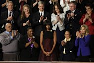 First lady Michelle Obama is applauded before President Barack Obama's State of the Union address during a joint session of Congress on Capitol Hill in Washington, Tuesday Feb. 12, 2013. Front row, from left are, Nathaniel Pendleton, Cleopatra Cowley-Pendleton, Mrs. Obama, Menchu Sanchez and Jill Biden. Second row, from left are, Oregon Gov. John Kitzhaber, Deb Carey, Apple CEO Tim Cook, Amanda McMillan, Lt. Brian Murphy and Marie Lopez Rogers. (AP Photo/Jacquelyn Martin)