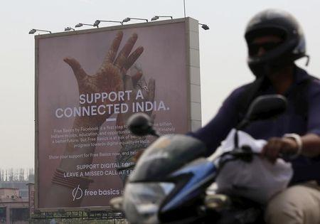 A motorist rides past a billboard displaying Facebook's Free Basics initiative in Mumbai, India