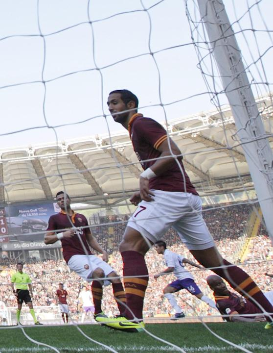 Fiorentina midfielder Juan Vargas, of Peru, second from right framed by AS Roma defender Mehdi Benatia, of Morocco, celebrates after scoring during a Serie A soccer match between AS Roma and Fiorentin