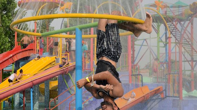Families cool themselves at a water park in Amritsar on May 24, 2015 as northern Indian states and other parts of India reel under hot summer conditions