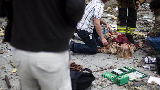 A victim is treated outside government buildings in the center of Oslo, Friday July 22, 2011, following an explosion that tore open several buildings including the prime minister's office, shattering windows and covering the street with documents. (AP Photo/Fartein Rudjord)