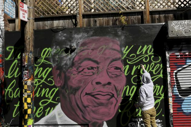 A muralist paints a tribute to Nelson Mandela in Clarion Alley in the Mission neighborhood in San Francisco