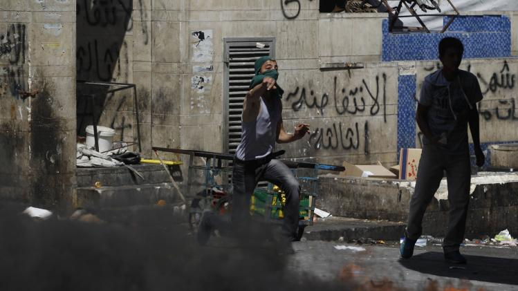 Protester hurls a stone toward Palestinian riot police trying to stop the protesters from clashing with Israeli troops during a protest against the Israeli offensive in Gaza, in West Bank city of Hebron