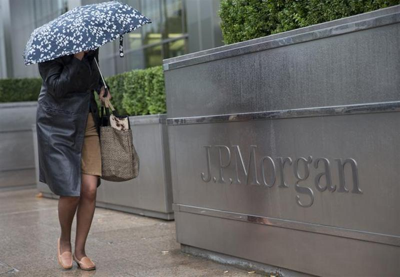 A pedestrian walks past the Canary Wharf offices of JP Morgan in London September 19, 2013. REUTERS/Neil Hall