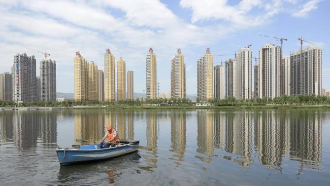 A man rows a boat on a river in front of new properties in Taiyuan