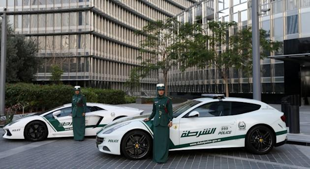 Emirati female police officers pose in front of Ferrari (R) and Lamborghini (L) police vehicles at the foot of the Burj Khalifa tower  in the Gulf emirate of Dubai on April 25, 2013. Dubai police show