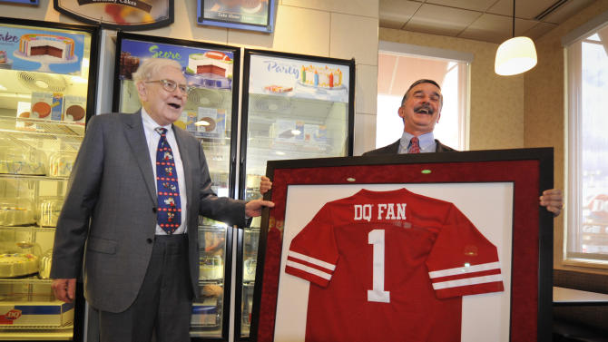 """IMAGE DISTRIBUTED FOR DAIRY QUEEN - Berkshire Hathaway's Warren Buffett and Dairy Queen's CEO John Gainor look at a jersey on Monday, May 20, 2013 in Omaha, Neb. Buffet helped launch the """"The First S'mores Blizzard of Summer"""" and was celebrated as Dairy Queen's number one fan. (Dave Weaver/AP Images for Dairy Queen)"""