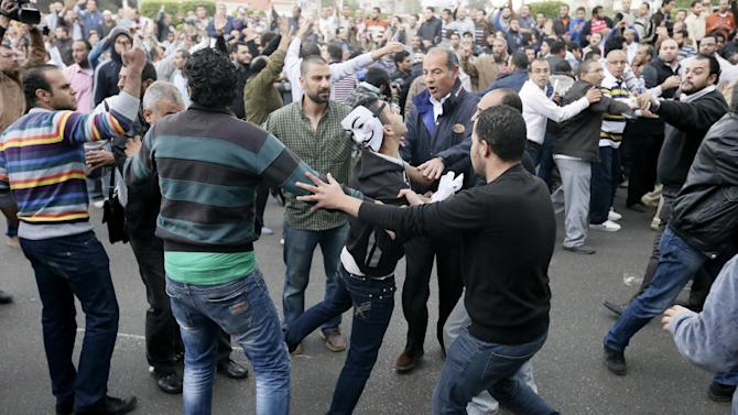Egyptian President Mohammed Morsi's supporters, background, and opponents, foreground, clash outside the presidential palace, in Cairo, Egypt, Wednesday, Dec. 5, 2012. Wednesday's clashes began when thousands of Islamist supporters of Morsi descended on the area around the palace where some 300 of his opponents were staging a sit-in. (AP Photo/Hassan Ammar)