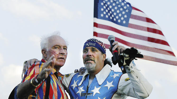 FILE - In this July 28, 2006 file photo, daredevil Evel Knievel and his son and fellow daredevil Robbie embrace at the top of the landing ramp prior to Robbie's successful 180-ft jump during the fifth annual Evel Knievel Days in Butte, Mont. A struggle for control over the festival, that draws thousands of stuntmen, wannabes and fans paying homage to Evel Knievel in his Montana hometown, has led organizers to turn over the event to the famous daredevil's family. Chad Harrington, executive director of Evel Knievel Week Inc., said the group decided Tuesday, April 8, 2014 to cut ties with the Evel Knievel Days event. (AP Photo/The Montana Standard, Walter Hinick, File)