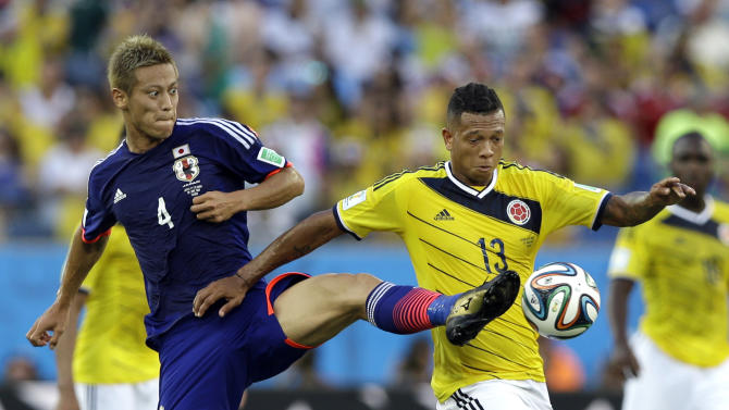 Japan's Keisuke Honda, left, and Colombia's Fredy Guarin battle for the ball during the group C World Cup soccer match between Japan and Colombia at the Arena Pantanal in Cuiaba, Brazil, Tuesday, June 24, 2014. (AP Photo/Kirsty Wigglesworth)