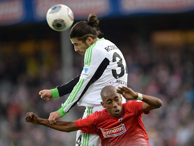Wolfsburg's  Ricardo Rodriguez, left, challenges for the ball with Freiburg's  Gelson Fernandes during the German first division Bundesliga soccer match between SC Freiburg and VfL Wolfsburg i