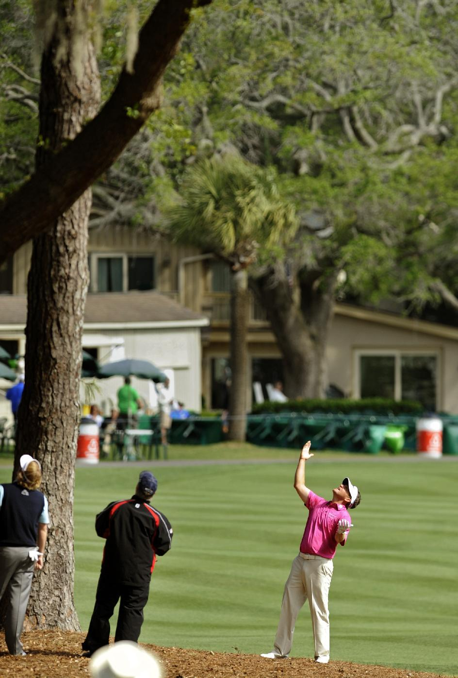 Jason Bohn, right, looks for his ball in a pine tree after his shot from the 10th fairway during the final round of the RBC Heritage golf tournament in Hilton Head Island, S.C., Sunday, April 21, 2013. (AP Photo/Stephen Morton)