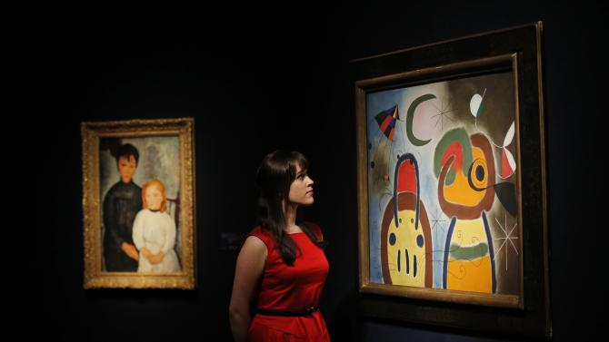"""A member of staff poses with """"L'oiseau au plumage deploye vole vers l'arbre argentee"""" by Joan Miro at Christie's auction house in London"""