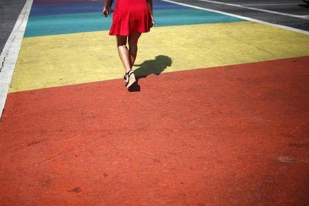 A person walks across a rainbow pedestrian crossing on a road in West Hollywood