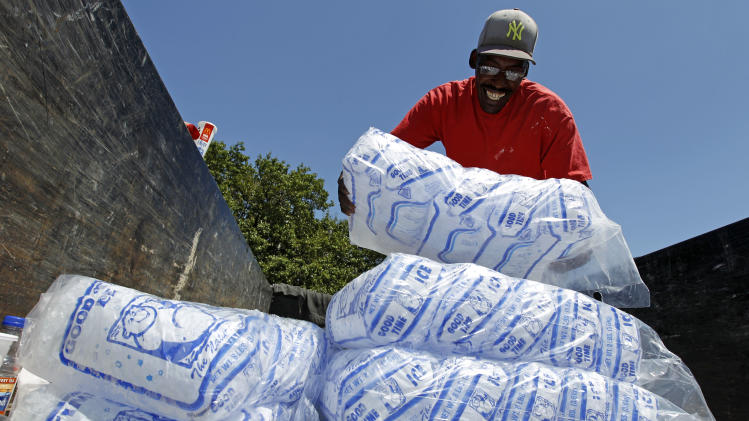 Baltimore city worker Bobby Carter gives away free bags of ice to residents at the Northwood Plaza shopping center in Baltimore on Monday, July 2, 2012.  Around 2 million customers from North Carolina to New Jersey and as far west as Illinois were without power Monday morning after a round of summer storms.  (AP Photo/Jose Luis Magana)
