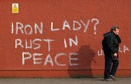 A pedestrian walks past graffiti refering to former British prime minister Margaret Thatcher in west Belfast, Northern Ireland, on April 9, 2013 a day following Thatcher's death