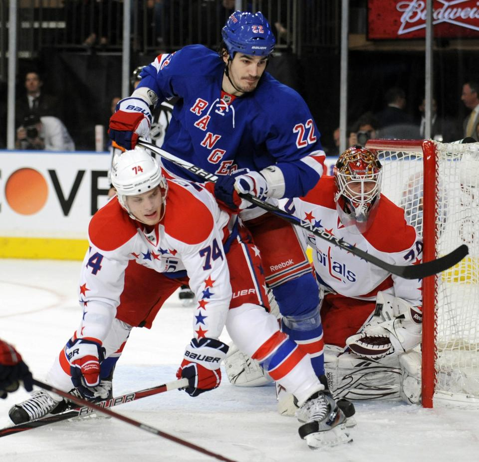 New York Rangers' Brian Boyle chacks Washington Capitals' John Carlson, left, as he screens goaltender Braden Holtby, right, during the second period of an NHL hockey game Saturday, April 7, 2012, at Madison Square Garden in New York. The Capitals defeated the Rangers 4-1.  (AP Photo/Bill Kostroun)