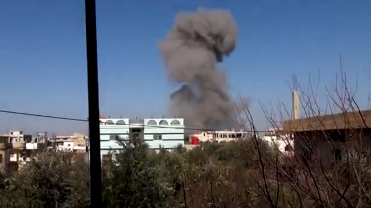 In this image taken from video obtained from the Ugarit News, which has been authenticated based on its contents and other AP reporting, smoke rises after an airstrike hit Daraa, Syria, on Monday, Jan. 14, 2012. (AP Photo/Ugarit News via AP video)