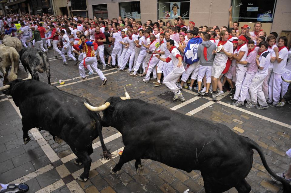 Revelers run on the Estafeta corner alongside Dolores Aguirre Yabarra ranch bulls during the first running of the bulls at the San Fermin fiestas, in Pamplona northern Spain, Saturday, July 7, 2012. (AP Photo/Alvaro Barrientos)