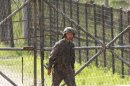 A South Korean army soldier passes by a barbed-wire fence in Paju, South Korea, near the border village of Panmunjom, Sunday, May 19, 2013. The South Korean military on Sunday have beefed up monitoring on North Korea and are maintaining a high-level of readiness to deal with any risky developments to guard against possibilities of additional missile launches and other types of provocations. (AP Photo/Ahn Young-joon)