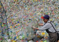 A volunteer of the Taiwan Buddhist Tzu Chi Foundation sorts through plastic bottles at a recycling plant in Taipei on February 28, 2013. Tzu Chi runs 5,400 recycling stations across Taiwan with the help of more than 76,000 volunteers