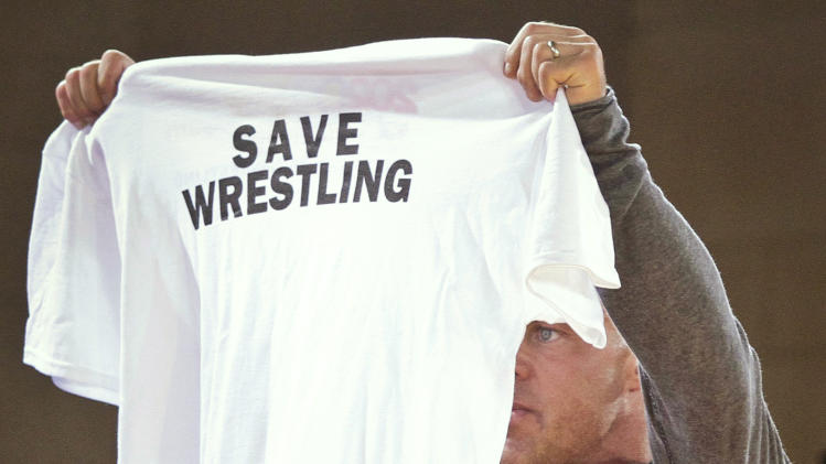 """Former Olympic gold medalist and professional wrestler Kurt Angle holds up a T-shirt during a three-nation wrestling exhibition at Grand Central Terminal on Wednesday, May 15, 2013, in New York. The event dubbed """"The Rumble on the Rails"""" marked the fourth straight year a New York City landmark was transformed into a wrestling meet to raise money for charity, with the last two in Times Square. In February, the International Olympic Committee recommended that the sport be dropped starting with the 2020 Games. (AP Photo/Bebeto Matthews)"""