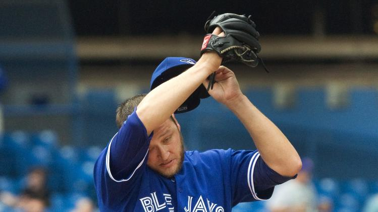 Toronto Blue Jays starting pitcher Mark Buehrle wipes his brow after giving up two runs to the Tampa Bay Rays in the seventh inning of a baseball game in Toronto, Saturday, Aug. 23, 2014. (AP Photo/The Canadian Press, Fred Thornhill)