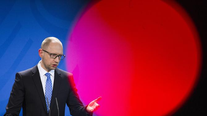 Ukrainian Prime Minister Arseniy Yatsenyuk gestures during a joined news conference with the German chancellor Merkel following a meeting at the chancellery in Berlin, Germany, Wednesday, April 1, 2015.  (AP Photo/Gero Breloer)