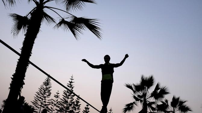 Man is silhouetted against the sun as he performs on a slackline at a park in Lima's Miraflores district