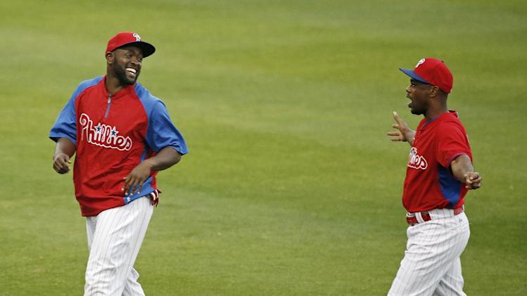 Philadelphia Phillies center fielder Tony Gwynn Jr., left, shares a laugh with Phillies shortstop Jimmy Rollins after they stretched on the field before a spring exhibition baseball game against the Baltimore Orioles in Clearwater, Fla., Monday, March 17, 2014