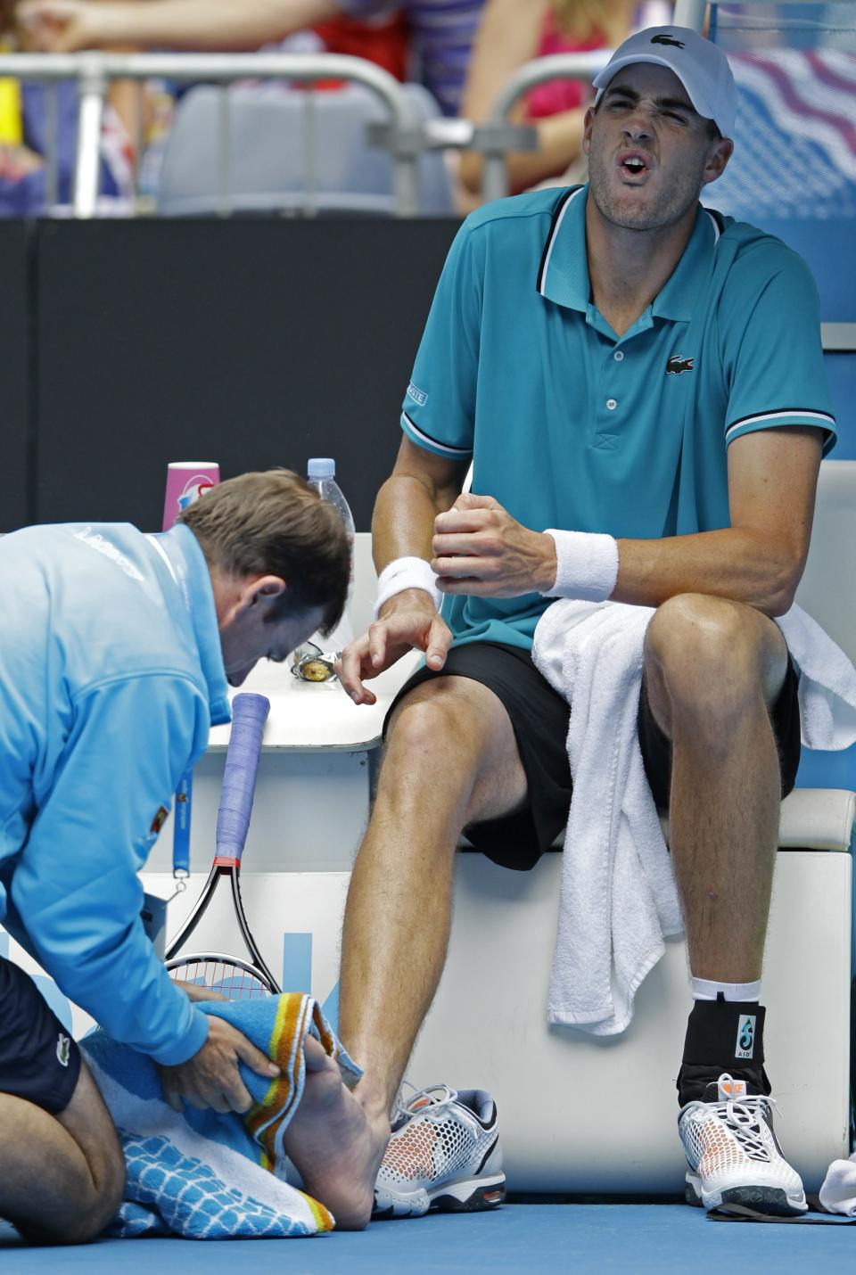John Isner of the US reacts as a trainer looks at his injured foot during his third round match against Spain's Feliciano Lopez at the Australian Open tennis championship, in Melbourne, Australia, Friday, Jan. 20, 2012. (AP Photo/Rick Rycroft)