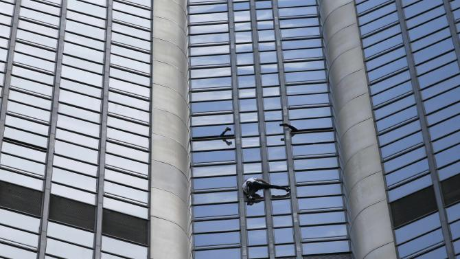 "People take pictures from the window as French climber Alain Robert, also known as ""Spiderman"", scales the Tour Montparnasse, a 210-metre (689 ft) building in central Paris"