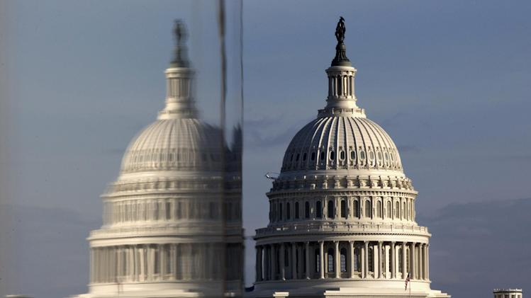 This photo taken Jan. 8, 2013, shows the Capitol reflected in the windows of the Newseum, on Pennsylvania Avenue in Washington, as a building wrap is installed in preparation of the President Barack Obama's second inauguration. (AP Photo/Jacquelyn Martin)