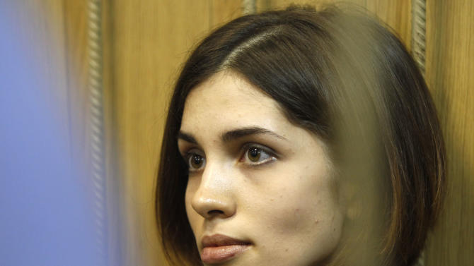 "Nadezhda Tolokonnikova, a member of the feminist punk band, Pussy Riot, sits behind bars in Moscow's Tagansky district court, Wednesday, June 20, 2012. She and two other band members face up to seven years on hooliganism charges after their February ""punk prayer"" at Moscow's Christ the Savior Cathedral in which they asked Holy Mary to deliver Russia from President Vladimir Putin.(AP Photo/Misha Japaridze)"