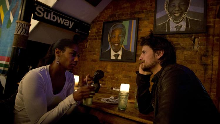People gather inside Madiba Restaurant named in honor of Nelson Mandela, after hearing news of Mandela's passing, in Brooklyn, New York