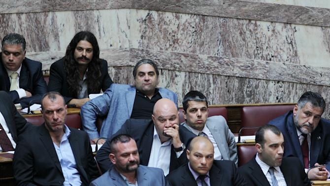 FILE - In this Friday, June 29, 2012 file photo shows lawmakers of the Golden Dawn extreme far-right party during a vote for deputy speakers at the Greek Parliament, in Athens. Greece's public order ministry on Monday, Sept 10, 2012 is withdrawing police guards who have been protecting the lawmakers of an extreme far-right party that has vowed violent intimidation against immigrant street vendors. (AP Photo/Thanassis Stavrakis, File)