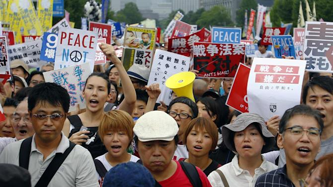 "Protesters stage a rally in front of the National Diet building in Tokyo, Sunday, Aug. 30, 2015.  Thousands of Japanese protested outside the parliament a set of security bills designed to expand the role the country's military. The bills - a cornerstone of Prime Minister's Shinzo Abe's move to shore up Japan's defenses in the face of growing threats in the region - are expected to pass next month despite criticism they undermine Japan's post-war pacifism. The placards read ""No war."" (AP Photo/Shizuo Kambayashi)"