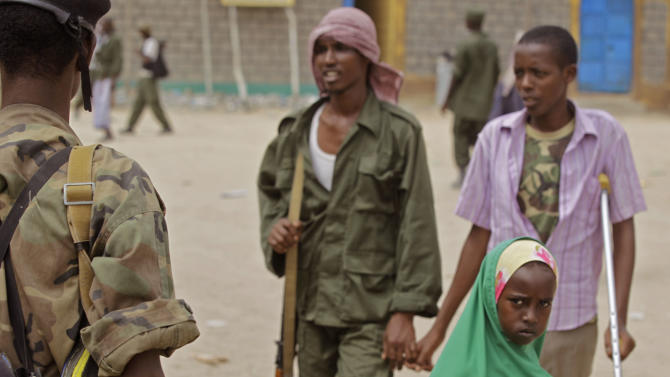 In this photo taken on Wednesday, July 27, 2011, Somalian transitional government force soldiers provide security as a girl walks by in the town of Dhobley, Somalia. Young Somalis with new uniforms and guns they say are paid for by Kenya's government are guarding the Kenya-Somalia border, a buffer zone of protection from Islamist militants. But many of the armed men don't get paid a salary and are preying on Somali refugees fleeing the famine. (AP Photo/Schalk van Zuydam)
