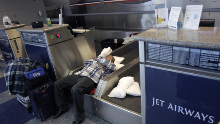An air passenger sleeps on a luggage conveyor belt at John F. Kennedy International Airport in New York, Monday, Dec. 27, 2010.  (AP Photo/Seth Wenig)