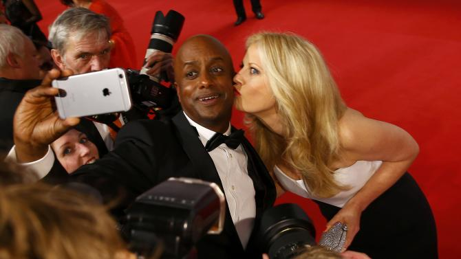 TV presenter Schoeneberger poses for selfie with German TV host Dibaba as he arrives for Golden Camera awards ceremony in Hamburg