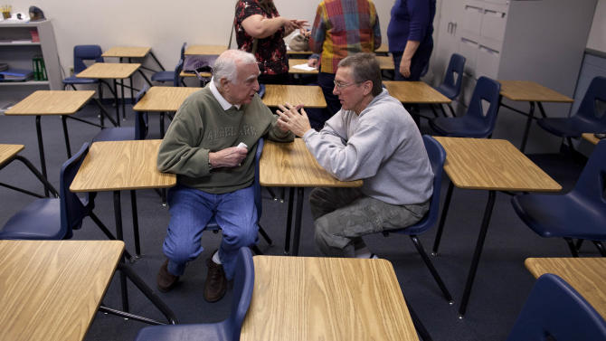 Jerry Robin, left, and Gary Reed continue to debate the candidates after a Republican caucus meeting at Del Sol High School, Saturday, Feb. 4, 2012, in Las Vegas.  (AP Photo/Julie Jacobson)