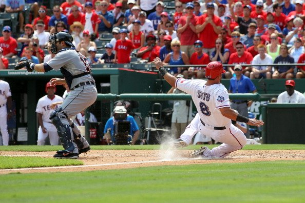 Geovany Soto #8 of the Texas Rangers slides safely into home as catcher Alex Avila #13 of the Detroit Tigers awaits the throw on August 12, 2012 at the Rangers Ballpark in Arlington in Arlington, Texa