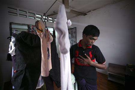 Bozor Mohammed from the Rakhine state in Myanmar puts his clothes, which were hung out to dry, inside his house after an interview in Kuala Lumpur