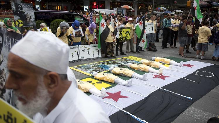 Protesters gather around effigies laid out on a Syrian flag during a demonstration marking the one-year anniversary of the chemical attacks in Syria, at Times Square in New York