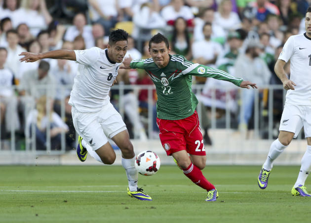 Mexico's Paul Aguilar, right, vies for the ball with New Zealand's Bill Tuiloma during their World Cup qualifying soccer match at Westpac Stadium, in Wellington, New Zealand, Wednesday, Nov. 20, 2013.