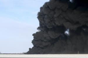 A plume of smoke rises from scene of a derailed train …